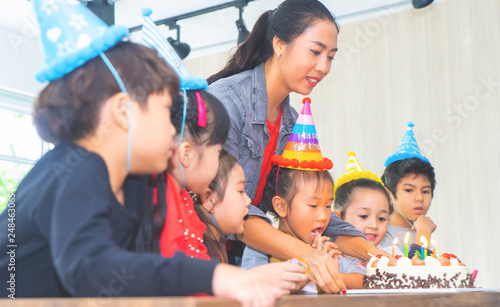 Foto Murales Group of children is blowing birthday cake in birthday  party singing happy birthday