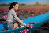 Young woman relaxing with beautiful lotus flower field at the Red Lotus Sea