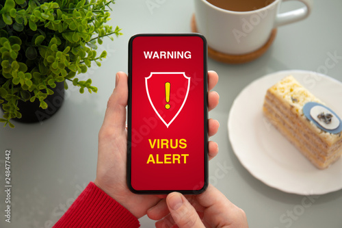 female hands holding phone with warning virus alert alarm - 248477442