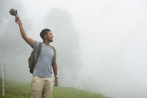 Foto Murales Tourist man backpacker walking alone on nature background