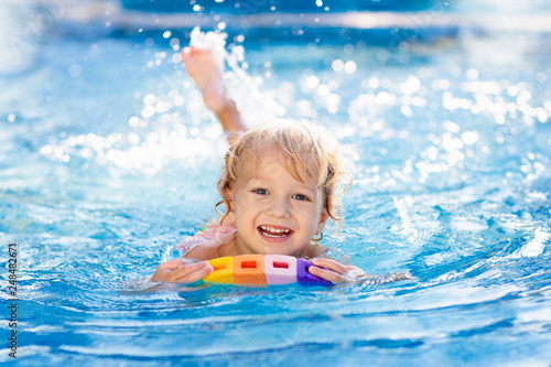 Child learning to swim. Kids in swimming pool.