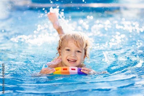 Leinwanddruck Bild Child learning to swim. Kids in swimming pool.