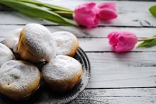 "Постер, картина, фотообои ""Cupcakes sprinkled with powdered sugar and pink tulips on a white table"""