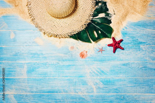 Foto Murales Top view of sandy beach with blue marine planks frame and summer accessories. Background with copy space and visible sand and wood texture. Border composition