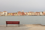 A red bench in the Giudecca island, watching the Canal Grande of Venice