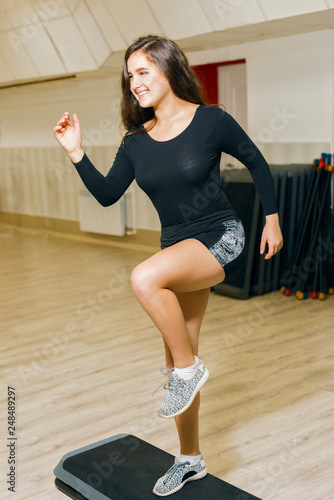 athletic girl in shorts engaged in fitness. woman taking steps on platform for step aerobics