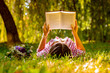 Young woman reading a book in the park with flowers - 248489895
