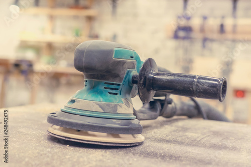 Worker grinds the wood of angular grinding machine - 248492675