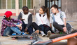 Leinwandbild Motiv girl and three boys hanging out outdoors and discussing something