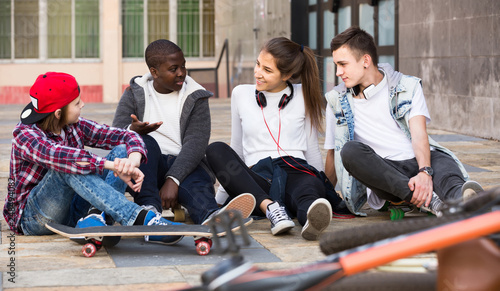 girl and three boys hanging out outdoors and discussing something