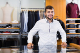 Positive young man seller in men's boutique - 248496616