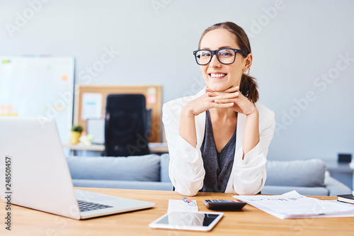 Cheerful young woman working in office at desk and looking at camera © baranq