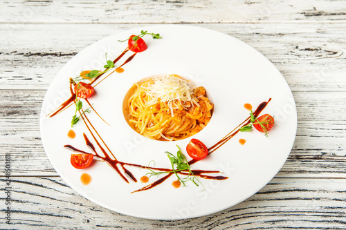 Salmon spaghetti in creamy tomato sauce on a white plate. Traditional Italian pasta with sauce, tomatoes and basil close-up and copy space. - 248508811