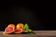 fresh grapefruits on wooden table with black background