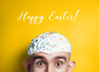 Funny Happy Easter concept. Emotional portrait of surprised bald man with easter cake on his head. half-face. Copyspace for text.