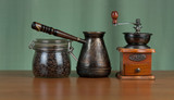 Coffee grinder, turk and cup of coffee on wooden background