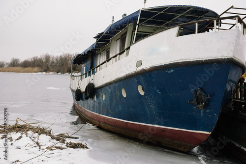 A small old ship is on the pier on the coast in winter © Богдан Ковенькин