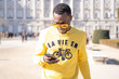 African funny man with sunglasses consults mobile phone in the streets of Madrid Spain.
