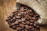 Coffee beans in coffee burlap bag on wooden table. - 248536833