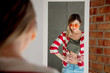 woman dressing up near mirror in sunglasses and jacket