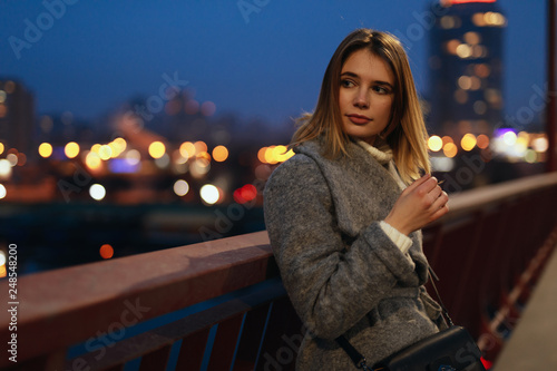 Woman standing in the ligths of the night city on bridge