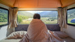 Leinwanddruck Bild - Young Asian man traveler staying in the blanket looking at mountain scenery through the window in camper van in the morning. Road trip in summer of South Island, New Zealand.