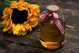 Sunflower oil in the bottle on the wooden table background.