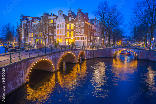 Canals of Amsterdam with dutch buildings at night in Amsterdam city, Netherlands © orpheus26