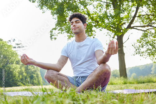 Foto Murales Young man making breathing yoga exercise