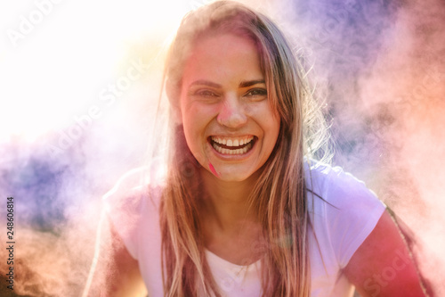 Leinwanddruck Bild Close up portrait of a happy woman playing holi