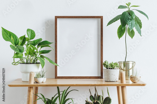 Scandinavian room interior with mock up photo frame on the brown bamboo shelf with beautiful plants in differents hipster and design pots. White walls. Modern and floral concept of shelfs.