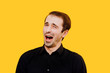 young man opens his mouth, shouts ok,standing on yellow background, copy space, positive emotions and happiness concept, isolated