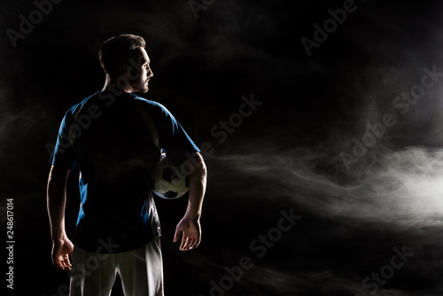 silhouette of football player holding ball on black with smoke © LIGHTFIELD STUDIOS