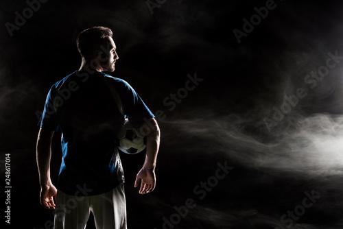 Leinwanddruck Bild silhouette of football player holding ball on black with smoke