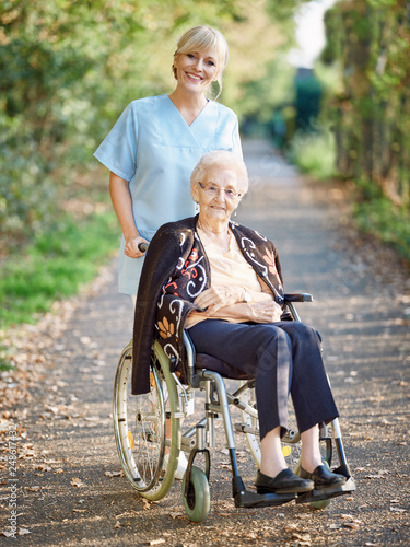 Pflegerin ist mit Seniorin im Rollstuhl unterwegs.