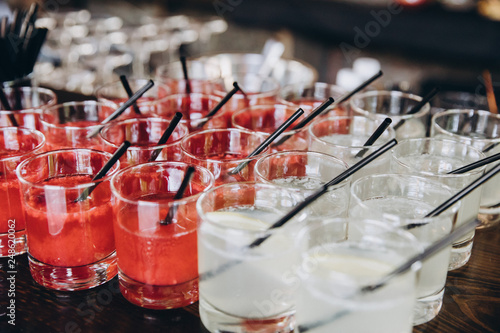 on the bar stand are glasses with white and red cocktails, straws in glasses © alexgukalov