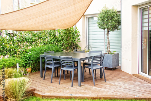 Modern terrace with dining table and chairs - 248625694