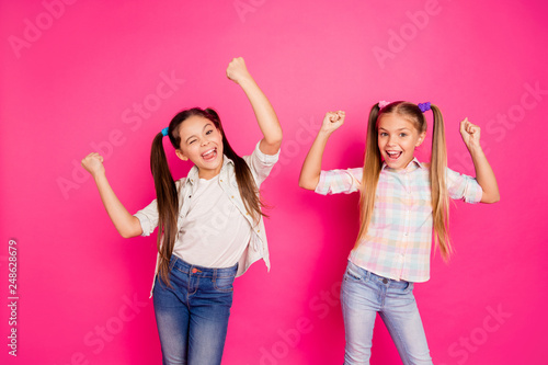 Close up photo two little age girls holiday dancing glad hands up children festive mood win boys video game wearing casual jeans denim checkered plaid shirts isolated rose vivid vibrant background - 248628679