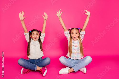 Leinwandbild Motiv Close up photo two little age she her girls hands arms up best friends sit floor legs crossed winners wearing casual jeans denim checkered plaid shirts isolated rose vibrant vivid background