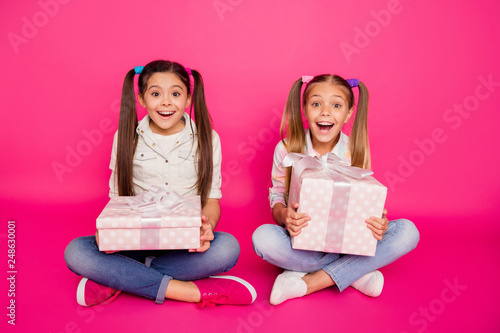 Leinwandbild Motiv Close up photo two wow faces little age she her girls holding hands arms large gift boxes best friends sit floor wear casual jeans denim checkered plaid shirts isolated rose vibrant vivid background