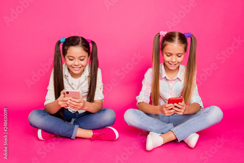 Leinwandbild Motiv Close up photo two people little age she her girls hold hands arms telephones chatting parents sit floor wear casual jeans denim checkered plaid shirts isolated rose vibrant vivid background