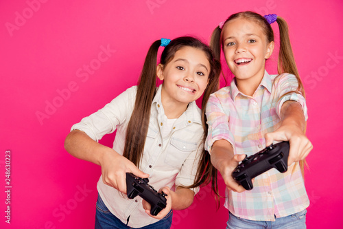 Leinwandbild Motiv Close up photo two people little age she her girls hold hands arms trying hard to win game not lose loser winner wear casual jeans denim checkered plaid shirts isolated rose vibrant vivid background