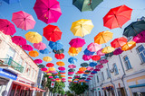 large number of colorful umbrellas hanging over a pedestrian street in the center of the old city. Summer concept