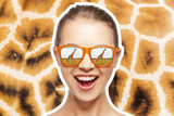 ecotourism and african safari concept - portrait of happy teenage girl in sunglasses looking at giraffes on giraffe skin texture background