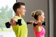 sport, fitness and people concept - couple with dumbbells exercising in gym - 248643234