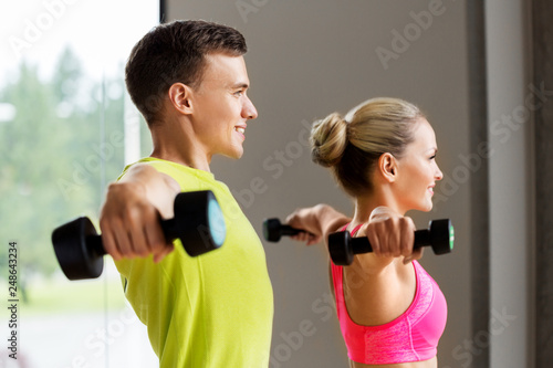 sport, fitness and people concept - couple with dumbbells exercising in gym