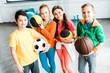 Leinwanddruck Bild - Excited children in sportswear posing with balls