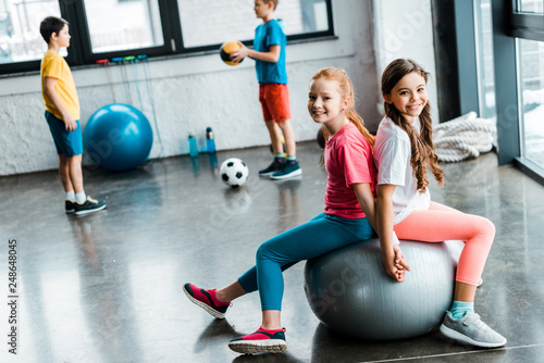 Laughing preteen friends sitting on fitness ball