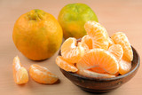 tangerines or orange fruit slices in a bowl on wooden table