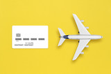 Model of airplane and credit card mock-up on yellow background